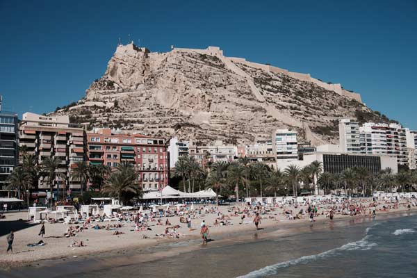 Imagen de una montaña, edificios y la playa con personas.