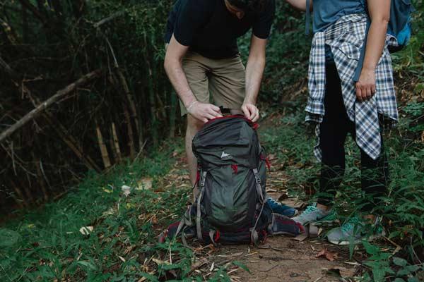 Dos personas en un bosque con una mochila.